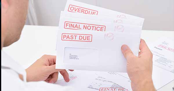 A man is holding three envelopes containing warnings of unpaid bills.