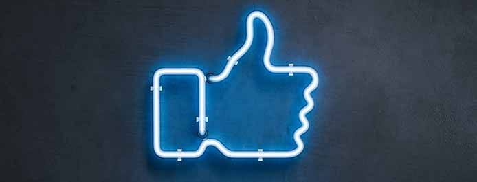 A blue neon sign shaped like Facebook's like button